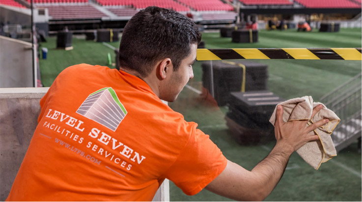 Level Seven staff member wiping down part of a stadium