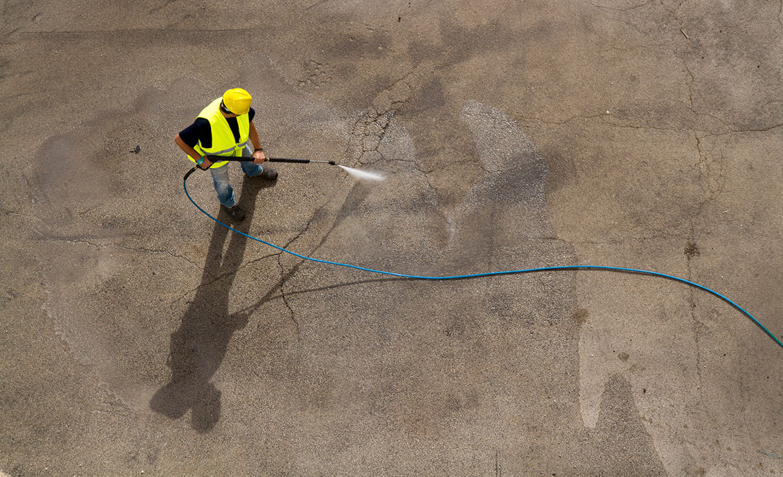 Level Seven staff member pressure washing a concrete surface